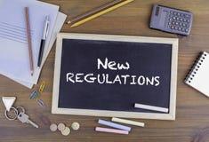 New Regulations. Chalkboard on wooden office desk Stock Photos