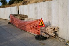 New Reinforced Concrete Wall, With Road Warning Sign. A new reinforced concrete wall beside road, with warning signs around stacked formwork, Greece stock photos