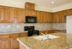 New or remodel residential kitchen. With oak cabinets, granite counters and black appliances Royalty Free Stock Photography