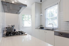 New renovated crisp white galley style kitchen Royalty Free Stock Photos