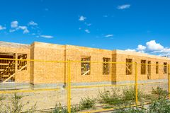 New residential building under construction with metal fence in front. Low rise wooden framework of the building on concrete base royalty free stock photography
