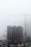 A new residential building under construction in the morning mist. Stock Image