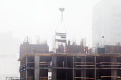 A new residential building under construction in the morning mist. Stock Photography