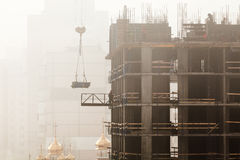 A new residential building under construction in the morning mist. Royalty Free Stock Photos