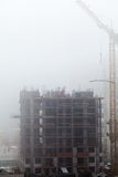 A new residential building under construction in the morning mist. Stock Photos