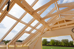New residential construction home framing against a blue sky. Roofing construction. Wooden construction. Stock Photos