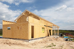 New residential frame house under construction against a blue sky. Royalty Free Stock Images
