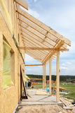 New residential frame house under construction against a blue sky. Stock Image