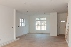 New Residential Home Interior Empty. Brand new house construction interior room with unfinished wood floors.  The HVAC electrical outlets and lighting fixtures Royalty Free Stock Images