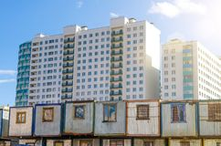 New residential multi-storey buildings, before them barracks for builders trailers. The concept of urbanization, contrast. Royalty Free Stock Images