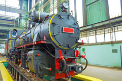 New retro locomotive. The new locomotive on the rails in the factory,photography Royalty Free Stock Photography