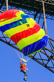 New River Gorge Bridge Colorful Base Jumper. A base jumper with a very colorful parachute floats down after leaping from the New River Gorge Bridge during their Royalty Free Stock Images