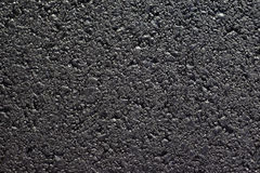 New Road. Close up background of a newly paved black asphalt blacktop street Stock Image