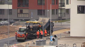 New road construction workers and equipment. VILNIUS, LITHUANIA - NOVEMBER 17, 2014: Asphalt spreader and roller machines on November 17, 2014 in Vilnius stock video footage