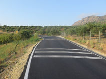 New road markings. Newly painted white road markings on rural tarmacked road in Andalusia, Spain Stock Image
