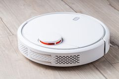 New robot vacuum cleaner. On clean wooden floor. Perspective view stock photography