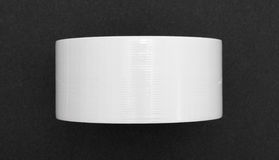 New roll of white duct tape on black craft paper Royalty Free Stock Images
