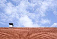 A new roof with chimney and red tiles of cloudy sky Royalty Free Stock Photos
