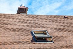 New roof with skylight, asphalt roofing shingles and chimney. Roof with mansard windows.  stock photo