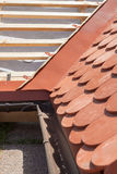 New roof under construction with wooden beams, waterproofing layer for corner and natural tile. Royalty Free Stock Photos