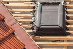 New roof under construction with wooden beams, waterproofing layer for corner, skylight and natural tile. Royalty Free Stock Image