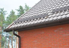 New roofing construction with rain gutter system, roof windows and roof protection from snow stock photography