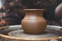A new, rough, clay vessel on a potter`s wheel. Pottery. Close-up royalty free stock photo