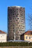 New round tower building under construction completely surrounded with building scaffolding and other small buildings with trees. In front on clear blue sky stock photos