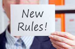 New Rules. Businesswoman with sign in the Office Stock Photo