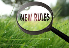 New rules. Magnifying glass with the word new rules on grass background. Selective focus Royalty Free Stock Image