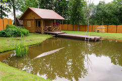 New rural bathhouse and pond with plank footbridge Stock Image