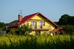 A new rural home with a blue sky. And green bushes Stock Photo