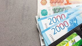 New Russian banknotes in denominations of 1000, 2000 and 5000 rubles and credit cards in a black leather purse close-up. Top view on a gray background with Stock Images