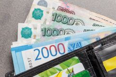 New Russian banknotes in denominations of 1000, 2000 and 5000 rubles and credit cards in a black leather purse close-up. Top view Stock Photo