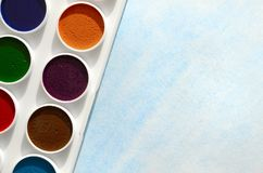 A new set of watercolors lies on a sheet of paper, which shows an abstract watercolor drawing in the form of blue strokes. The con stock image