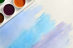A new set of watercolors lies on a sheet of paper, which shows an abstract watercolor drawing in the form of blue strokes. The con royalty free stock images