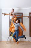 New settlers tries on new curtains to an eaves. Man and woman tries on new curtains to an eaves Stock Photography