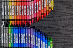 Crayons arranged on a grainy wooden board stock photography