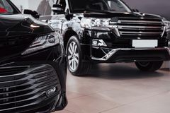 New shining beautiful cars stand near desk reception in car shop.  Stock Images