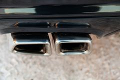 New shiny chrome pipes close-up after tuning and installation on the back of a black car brand Mercedes Benz model AMG in the tail stock image