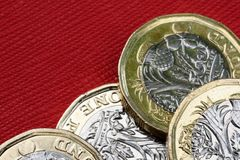 New UK One Pound Coin Currency. New shiny UK Pound Coin currency of silver and gold on a red background. Coins are designed to stop forgery of the English money Royalty Free Stock Photo