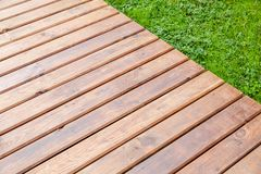 New shiny wooden boardwalk over park lawn royalty free stock photography