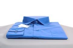 New shirt. New blue man shirt on grey podium, close-up, isolated on white Stock Photo