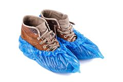 New shoe covers on the shoe. Blue protective shoe covers on men`s shoes isolated on white background Royalty Free Stock Images