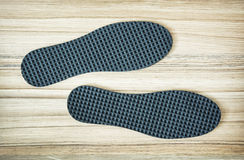 New shoe insoles on the wooden background. New orthopedic shoe insoles on the wooden background royalty free stock images