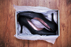 New shoes. Photo of a pair of new womens court shoes in a shoe box on rustic wooden floor Royalty Free Stock Images