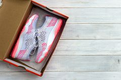 New shoes in boxed on wooden table background. New pink sneakers shoes in boxed on wooden table background stock photo