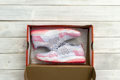 New shoes in boxed on wooden table background. New pink sneakers shoes in boxed on wooden table background stock photography