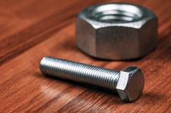 New silver nut and bolt. On wooden background royalty free stock photos