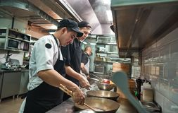 New skills. Two chef assistants cooking a new dish in a restaurant kitchen. Cooking School royalty free stock photo